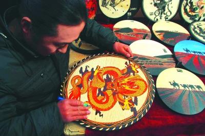 吉祥龙/2月28日,美术雕刻师邵林在敦煌市街头现场雕刻吉祥龙木板画。
