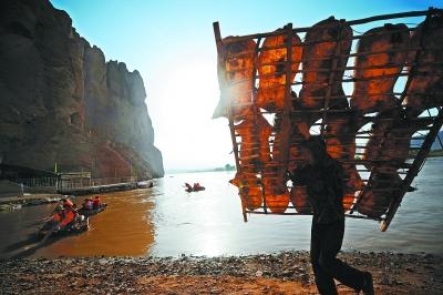 7月9日,在甘肃省景泰黄河石林景区,一名工作人员举着羊皮筏子走在