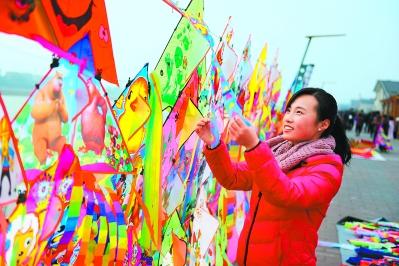 天水麦积区渭河风情线上挑选风筝的女孩(图)
