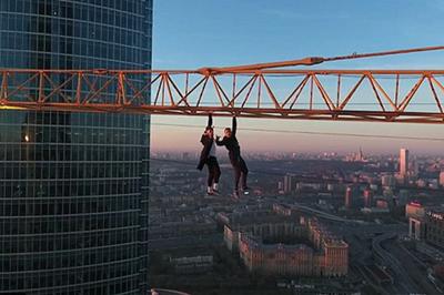 作死!俄两小伙百米高塔吊吊臂上行走做引体向上(组图)