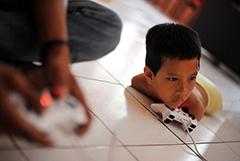 印尼无腿无臂男童用下巴玩游戏用嘴写字