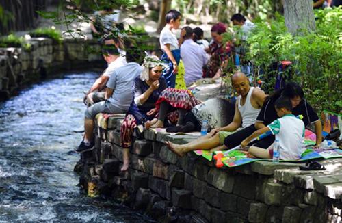 乌鲁木齐气温再破35摄氏度 市民公园内避暑