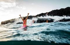 美国女子喷涌火山附近勇敢冲浪