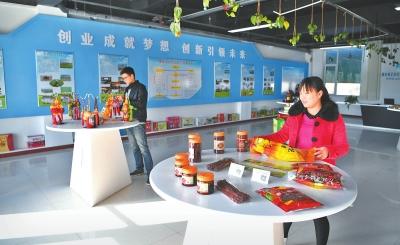 """张掖高台县""""金张掖北纬38°特产""""线下体验馆的工作人员展示农副产品(图)"""