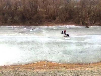 兰州黄河冰面3青年凿冰捞鱼(图)