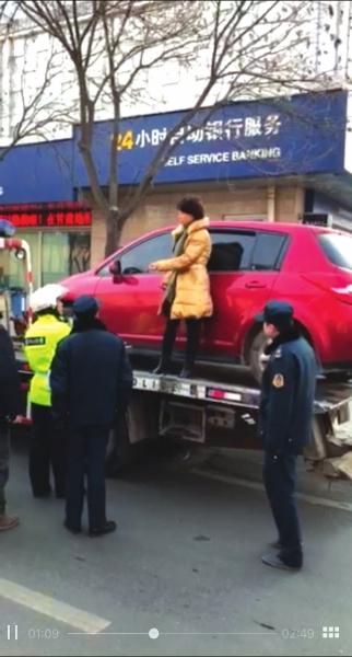 兰州一女司机涉嫌跑黑车 拒不配合检查 造成交通拥堵后站在拖车上阻拦民警执法(图)