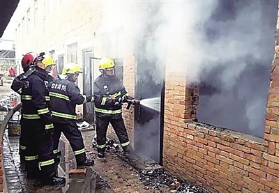 庆阳西峰区出租屋起火 消防队员抢出喷火气罐 (图)