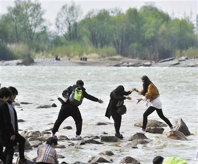 兰州两位市民为拍照远离岸边踏河石 游玩勿忘安全