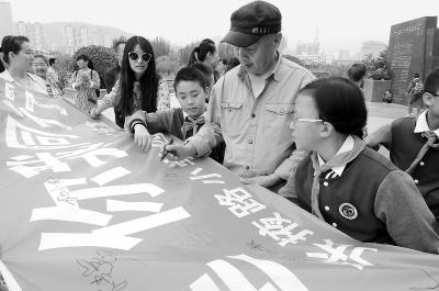 """兰州张掖路小学四年级二班同学及家长举行""""创建文明、你我同行""""主题签名活动"""
