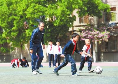 兰州市东郊学校的西班牙外教拉法给学生上足球课(图)