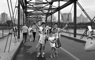 众多兰州市民在中山桥上休闲赏景享受清凉