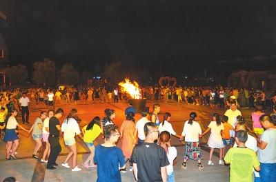 体验乡村旅游的人们在篝火晚会上跳起舞