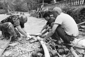 陇南市文县水务局工作人员与村民一起修复被洪水冲坏的供水管道