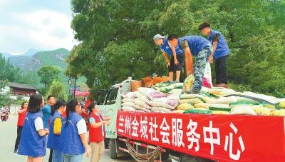 志愿者在文县天池镇王家庄村安置点给受灾群众发放物资