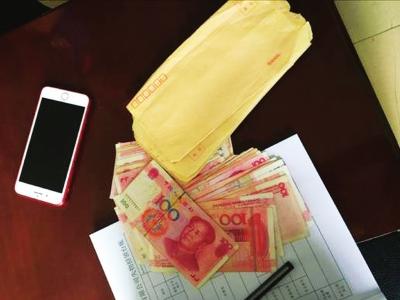兰州好的哥拾金不昧 捡到1.5万元现金和苹果手机全部归还失主