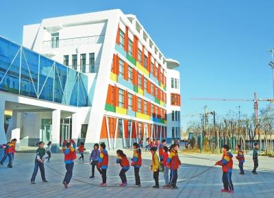 玉门市第三小学学生在新建成的教学楼下参加体育活动
