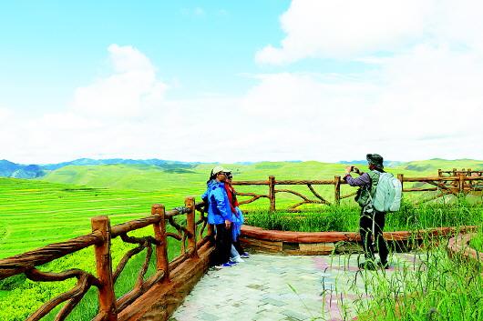 游客在甘南临潭县尕弯梁观景台观光留影
