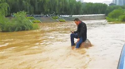 独坐河中石上无视水高浪急 兰州地方海事局将一名疑似醉酒男子强行救下移交警方