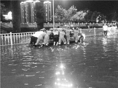 兰州:桥下积水出租车被困水中 交警消防及时救助