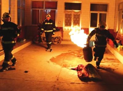 兰州新区西岔村里一煤气罐起火 消防员手拎冒火煤气罐排险情