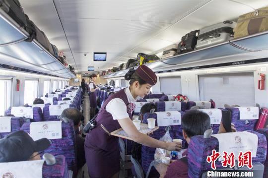 图为列车工作人员为旅客提供服务。 宋佳龙 摄