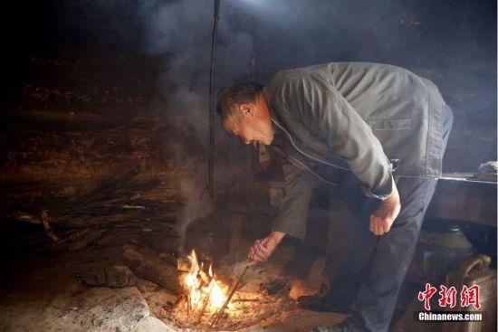 图为田永平在简易小木屋中生火烧水。冉创昌 摄