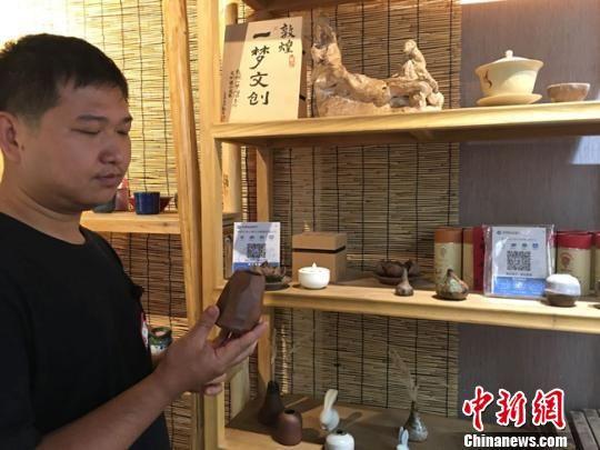 图为月牙泉小镇上的敦煌文化痴迷者叶金盛展示文创产品。 张婧 摄
