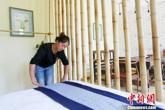 图为八月上旬,杜喜梅正在整理民宿床铺,准备迎接新客人入住。 高展 摄