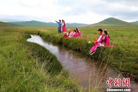 游客在狼渡湿地草原换上民族服装拍照留念。 包新田 摄
