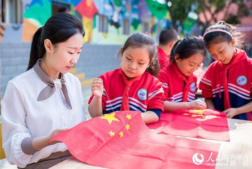 呼和浩特市玉泉区南茶坊小学师生以绣制国旗的方式庆祝新中国70华诞。