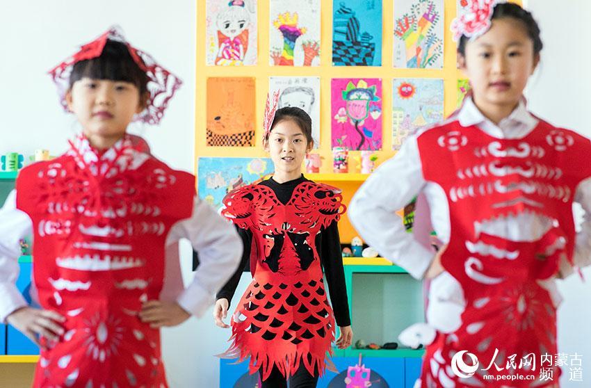 呼和浩特市玉泉区恒昌店巷小学剪纸社团的学生在展示创意剪纸服饰。