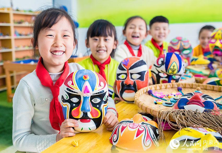 呼和浩特市玉泉区通顺街小学学生在展示绘制的戏剧脸谱作品。