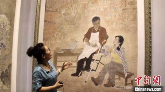 图为王亚林介绍她的创意绘画。 高莹 摄
