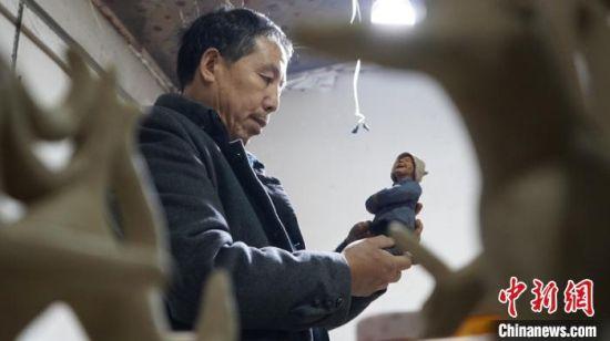 图为赵旭辉介绍他的泥塑作品。 魏建军 摄