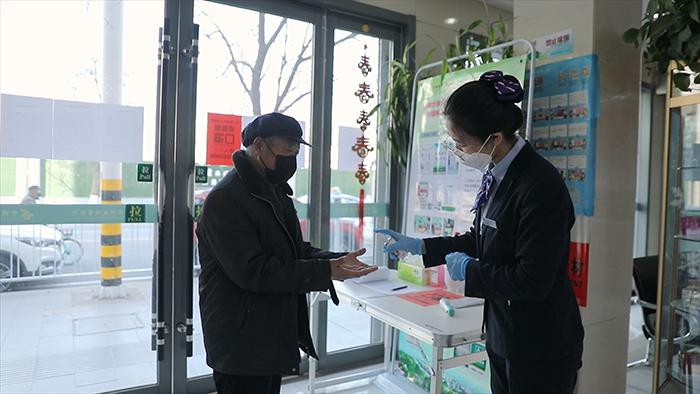 邮储银行甘肃省分行工作人员为客户消毒