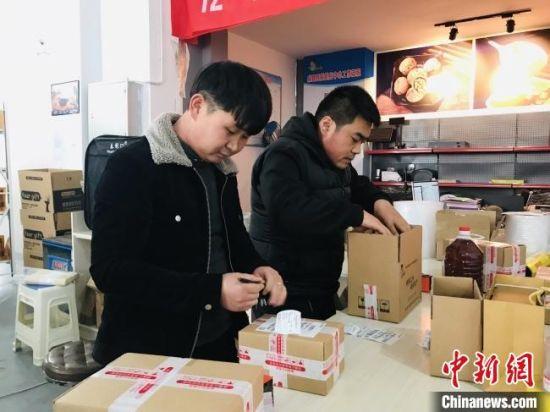 图为陇南市成县返乡青年正在电商企业包装货物。(资料图) 闫姣 摄