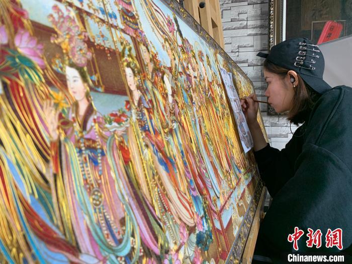 将唐卡、掐丝珐琅、平遥推光漆三项传统工艺相结合,创作出独具特色的金丝珐琅画。 王惠琳 摄