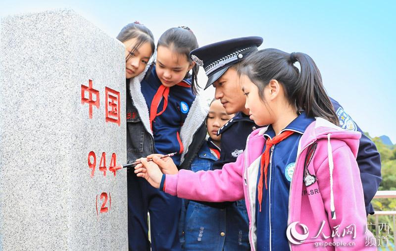 民警与学生们一起描红界碑。范先芳摄