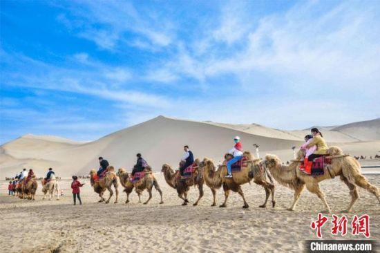 图为游客骑骆驼畅游鸣沙山,观赏敦煌丝路风情,大漠壮美风光。 王斌银 摄