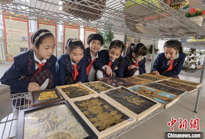 图为兰州新区实验小学小学生欣赏同学手工作品。 刘玉桃 摄