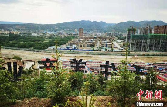 图为广河县康家模式的养殖区域与城区隔河相望。 艾庆龙 摄