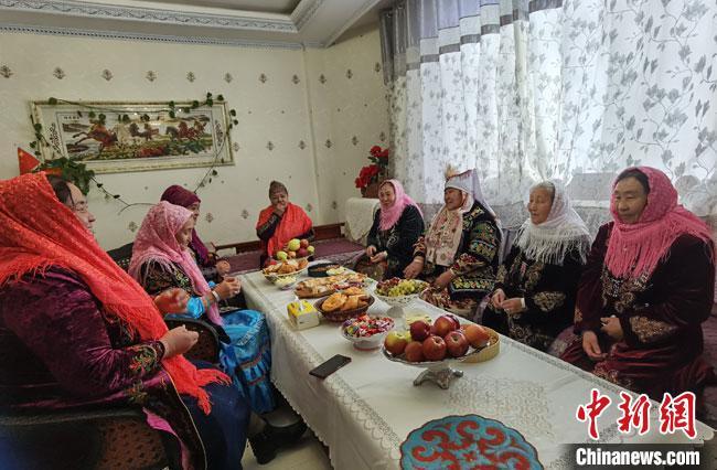 图为10月12日,阿克塞县民族新村一座时尚靓丽的别墅内,一户哈萨克族人家其乐融融的聚会场景。 冯志军 摄